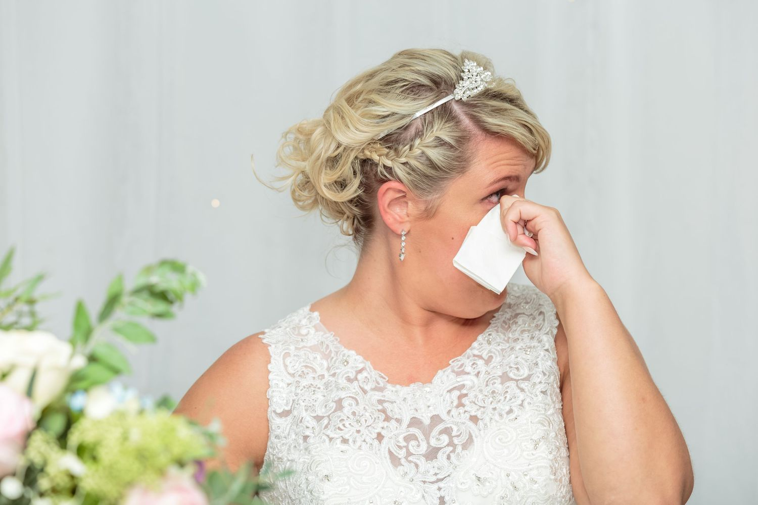 bride wipes a tear away from her eye with a napkin during her fathers speech