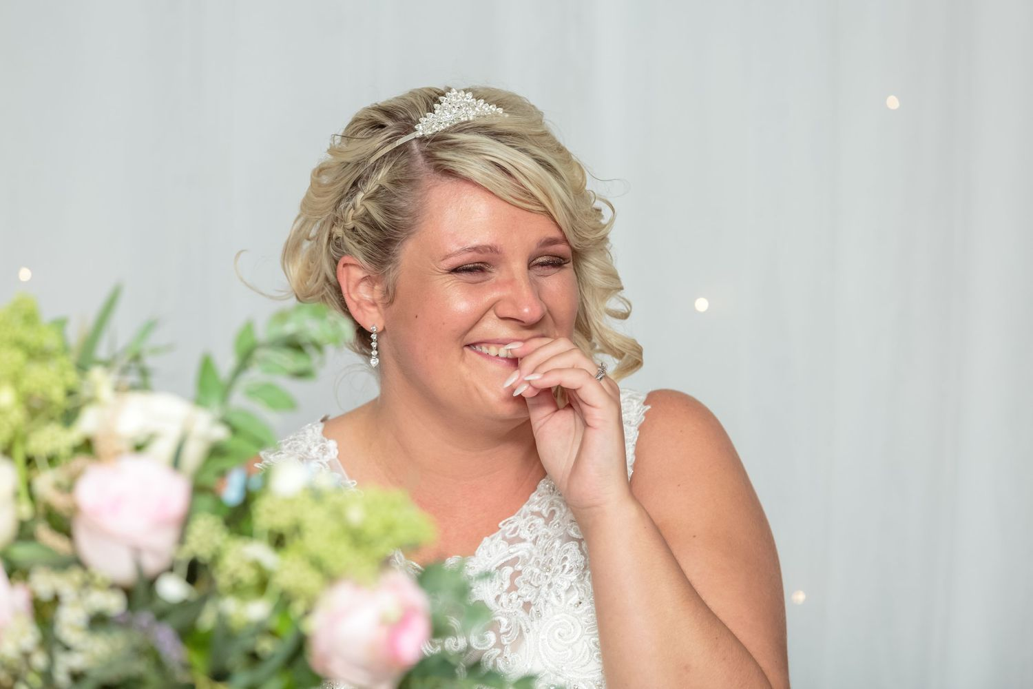 bride laughing with tears in her eyes puts her hand to her mouth during the wedding speech