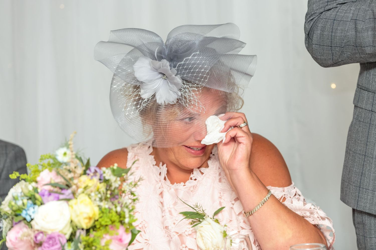grooms mother wipes tears away with her napkin during the wedding speeches at ribby hall