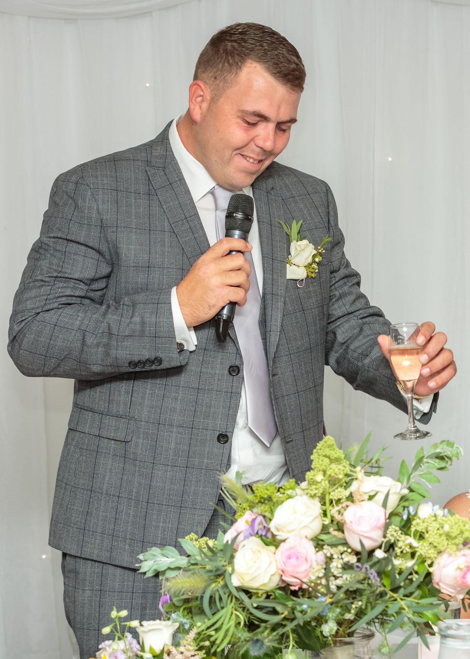 groom wearing a grey suit gives his speech mic in one hand glass of champagne in the other