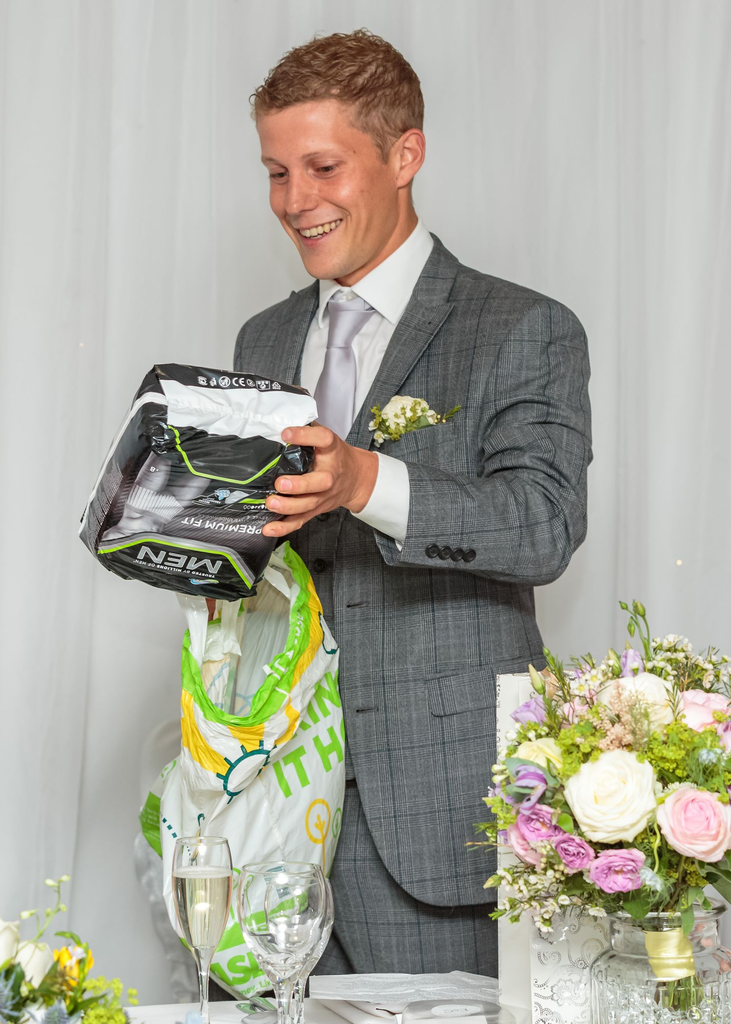 best man takes a pack of tena incontinence pads for men out of a carrier bag during his speech