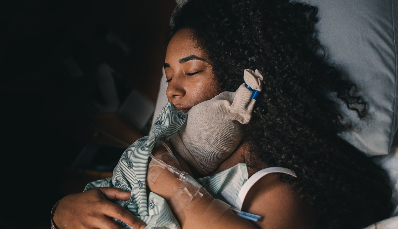 woman with eyes closed holding newborn on chest in hospital bed
