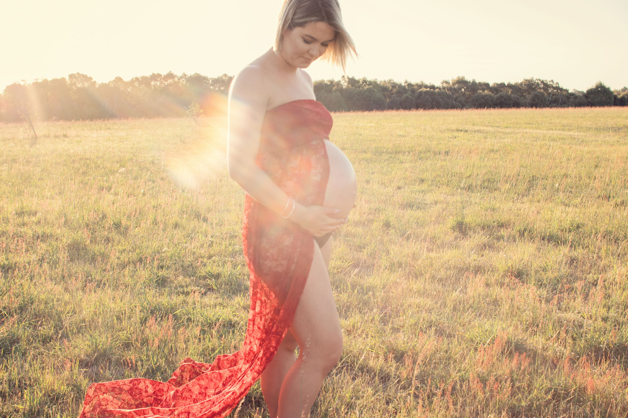 pregnant woman embracing belly in red dress