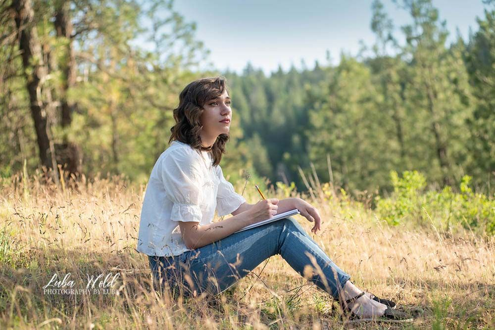 high school senior girl sitting on a hill in Post Falls outdoor studio dreaming or drawing photographer luba wold