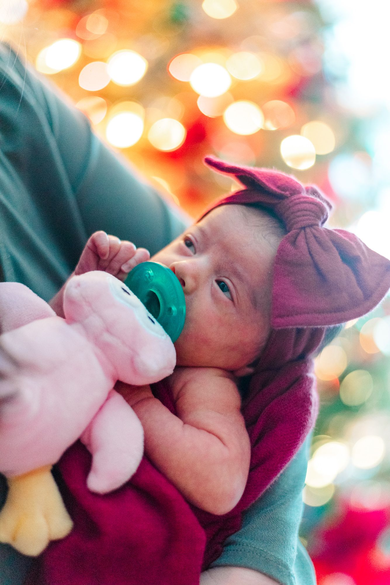 Lifestyle father holding newborn baby in pink wrap in front of Christmas tree in Pittsburgh, Pennsylvania