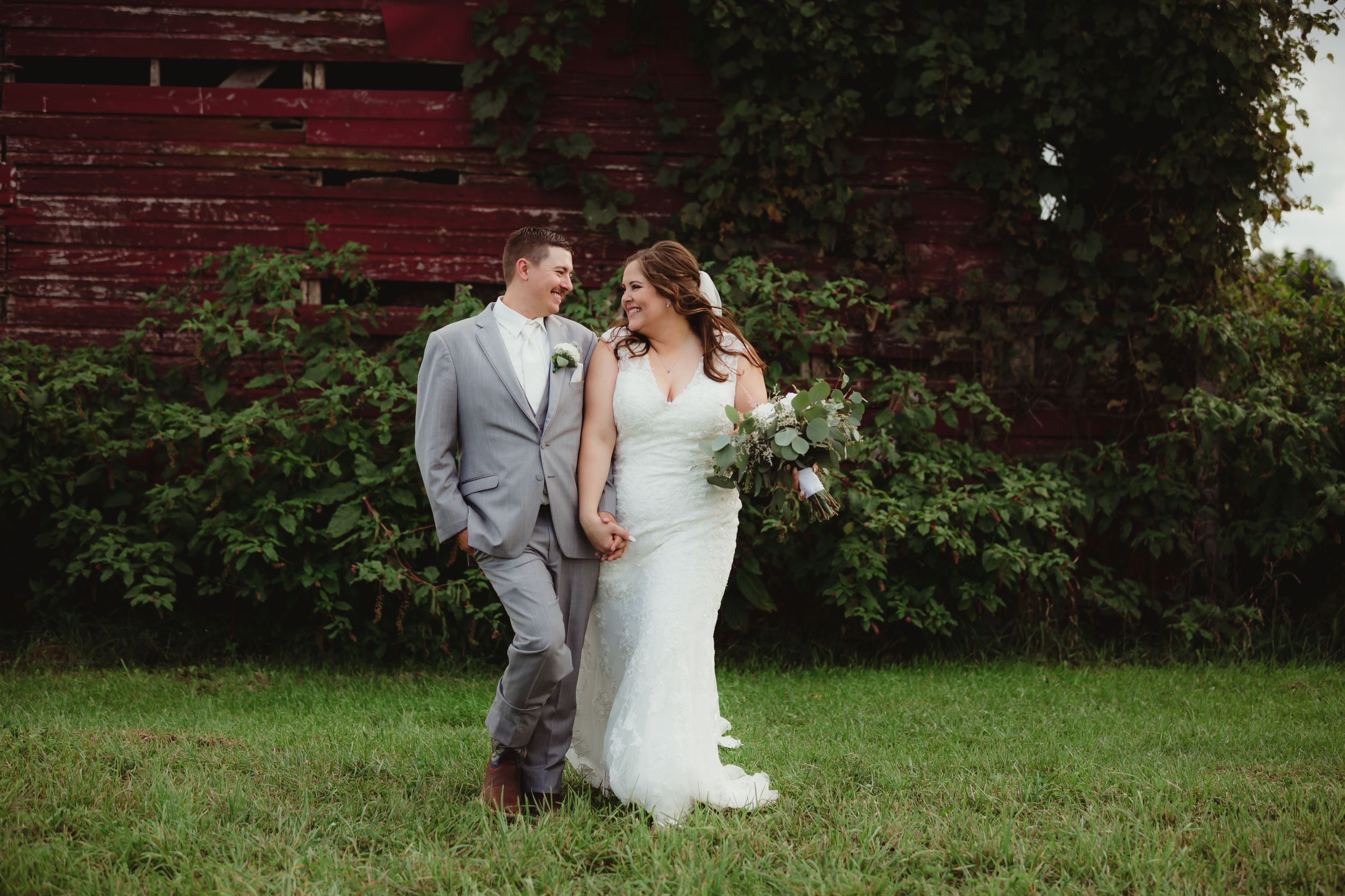 Bride and groom holding hands, walking, and smiling at each other in front of the old barn.