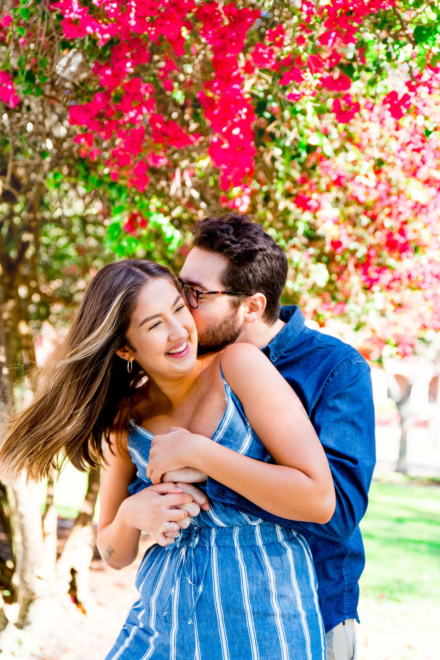 young man kissing woman's neck under pink flower tree at Vinoy Park, St Pete engagement photos