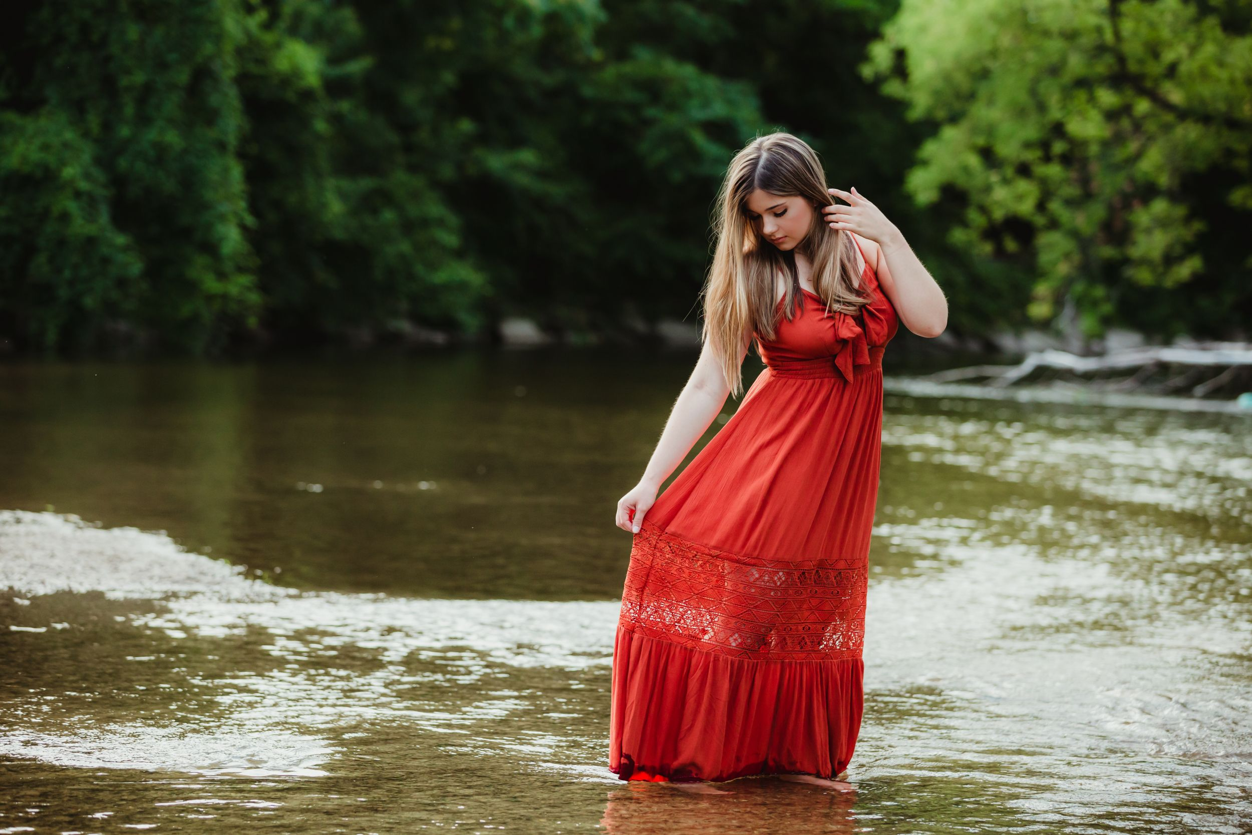 High school senior girl in a red dress standing in a river. She is holding the bottom of her dress out and looking down.
