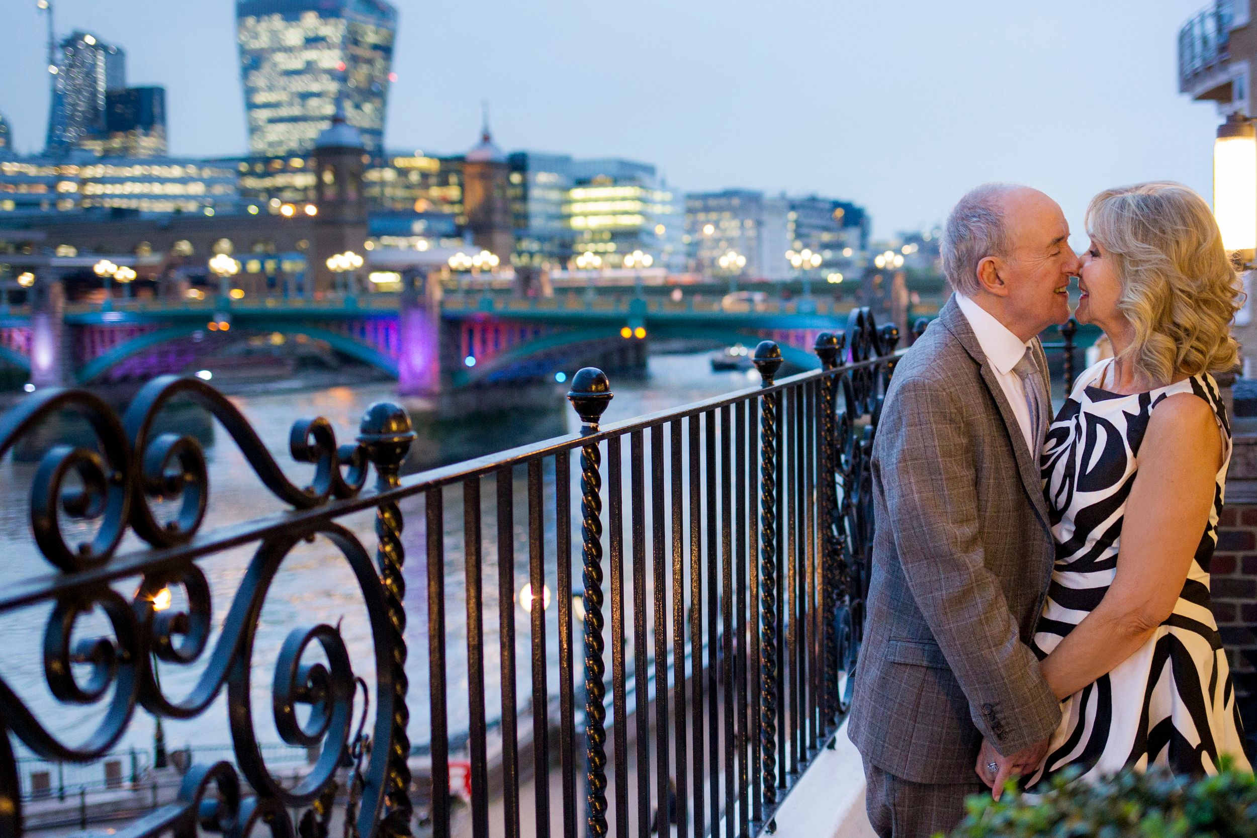 Bride and groom share a kiss on a balcony in front of the London skyline at dusk - Wedding Photography