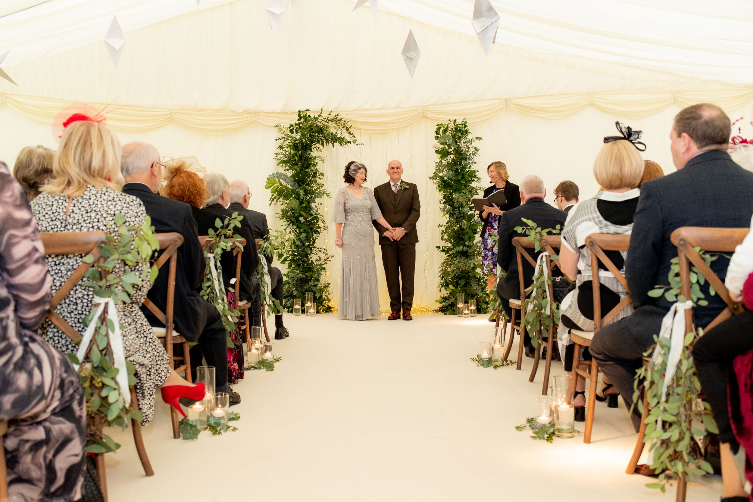 Bride and groom stand at the end of the alter in a marquee during their ceremony - Wedding Photography
