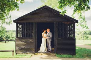 A bride and groom portrait in the doorway of the outhouse on a golf course - Wedding Photography