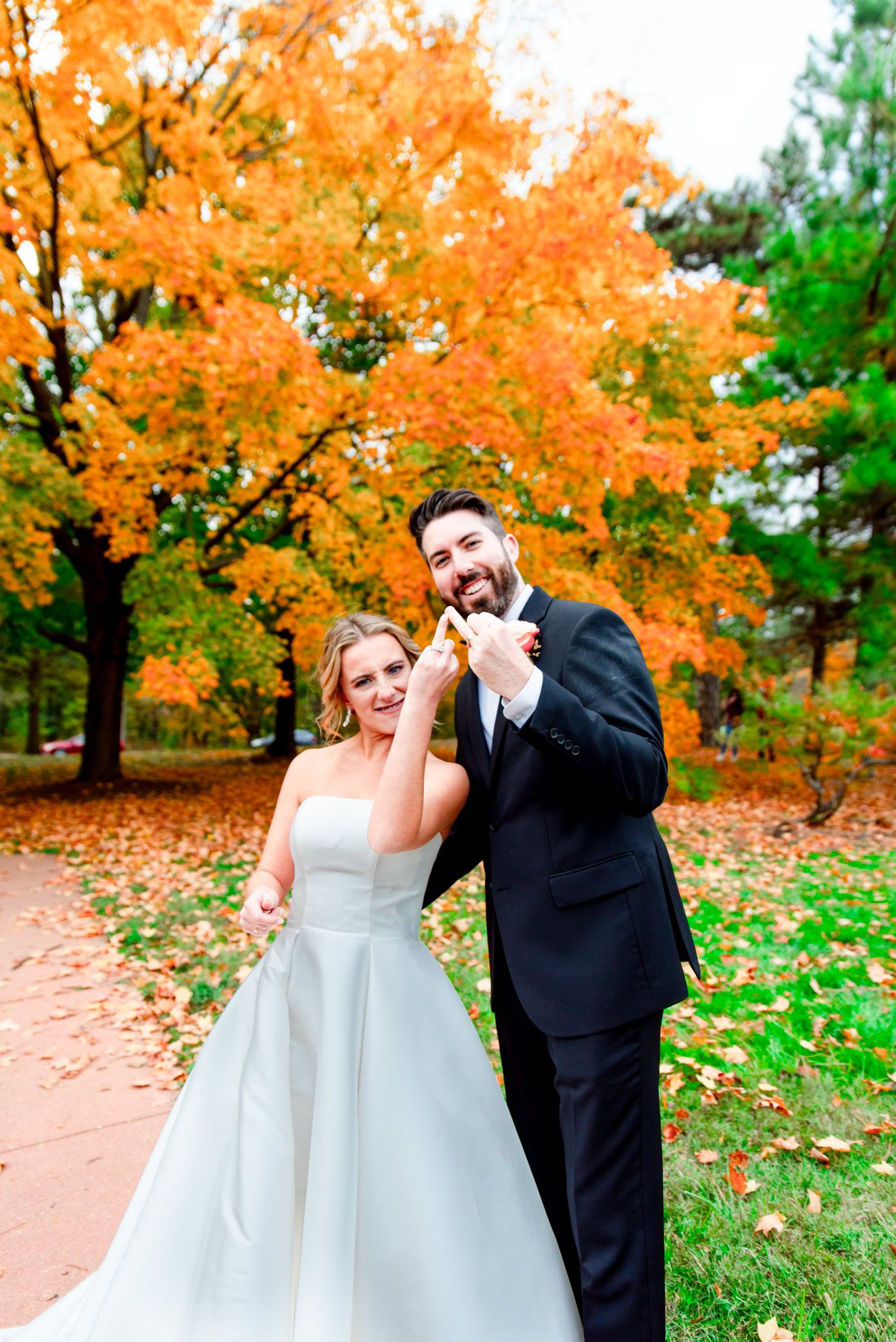 bride and groom hold up ring fingers in front of bright orange tree