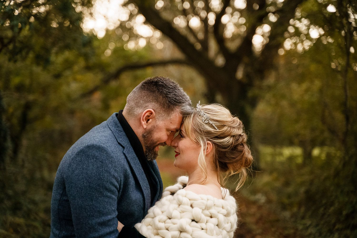 A newly wed couple embrace during golden hour at their winter wedding.