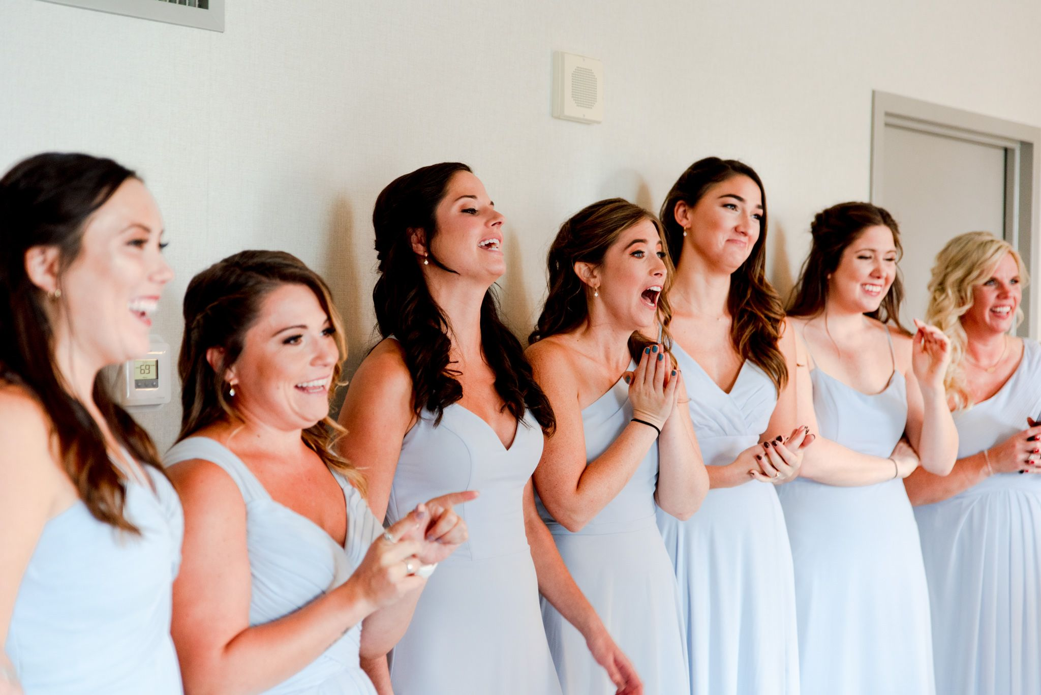 7 bridesmaids in light blue dresses smiling and clapping after seeing the bride
