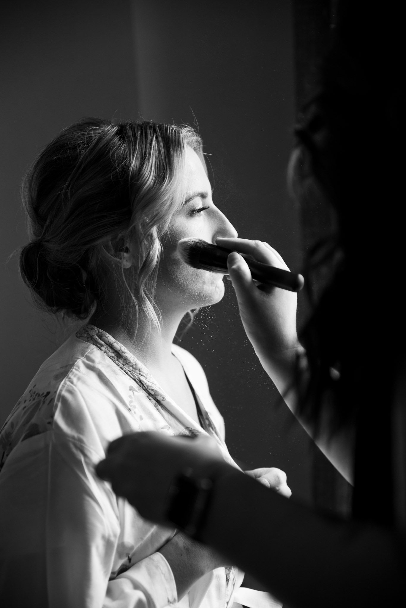 black and white image of bride getting blush on her face and makeup fallout in the light