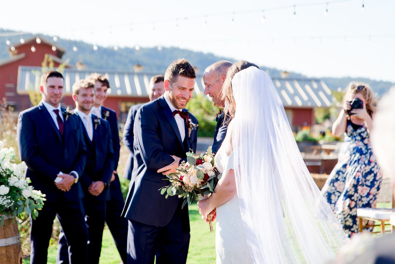groom in navy suit shaking father of bride's hand and laughing