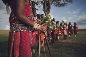 Masai morans all with floral bouquets and spears at a wedding ceremony in Masai Mara