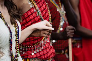 bride holding the hands of a masai warrior at her wedding in Masai Mara