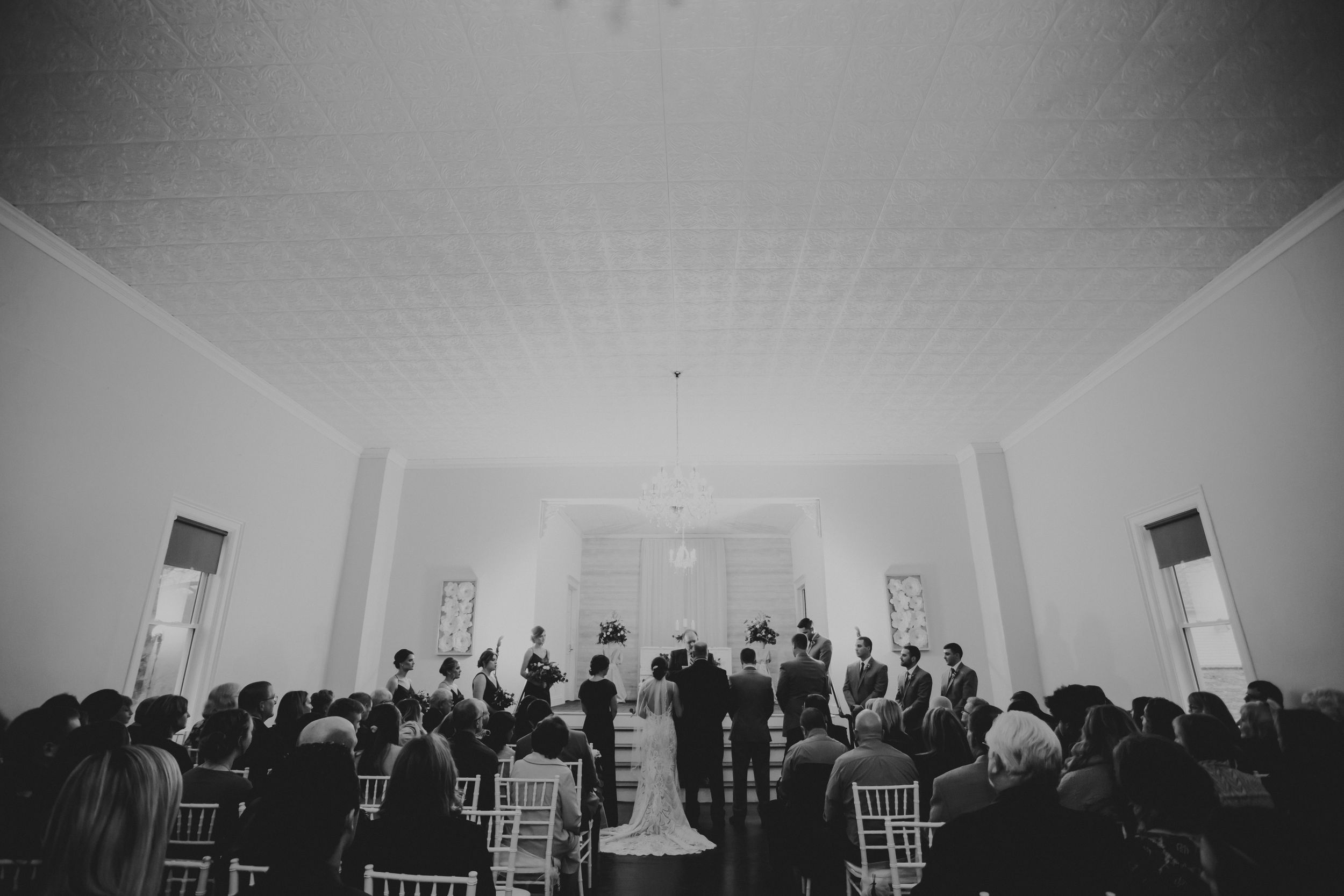 Black and white photo of a wedding ceremony happening inside the Graham Banquet Center.