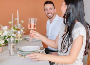 couple clinking wine glasses at dinning table