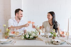 couple clinking wine glasses at table setting