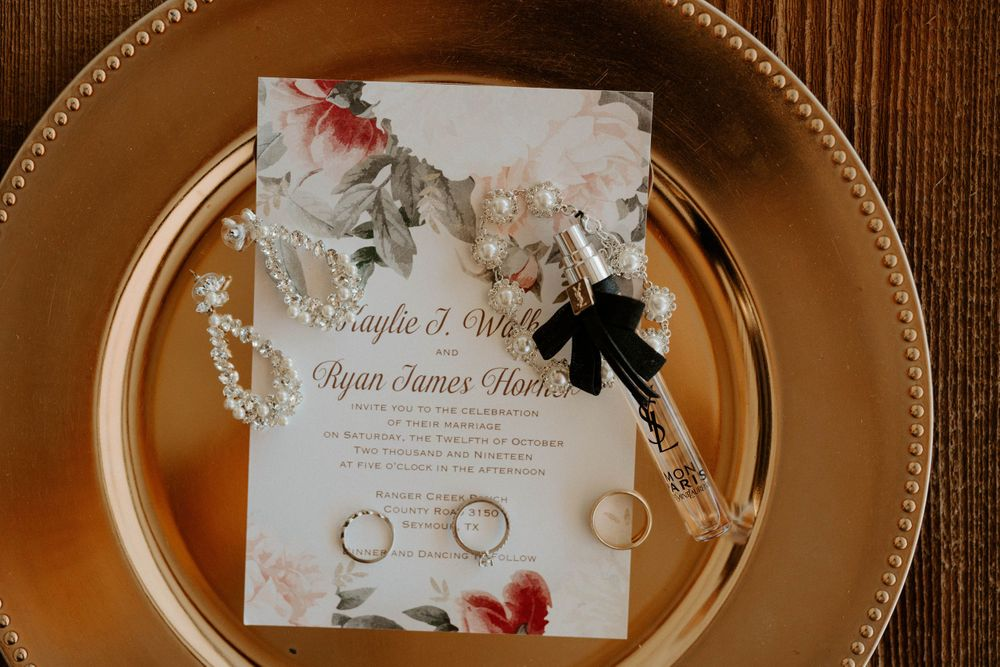 Invitation, rings, earrings, and perfume detail shot