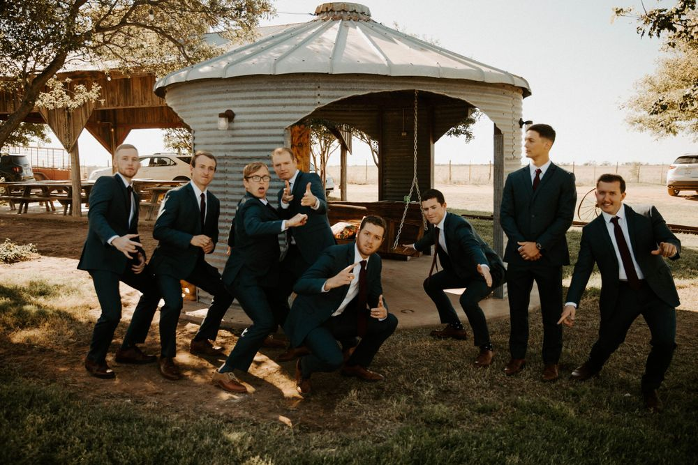 Groom and groomsmen in silly pose before wedding ceremony at The Reserve at Ranger Creek Ranch venue in Seymour, Texas