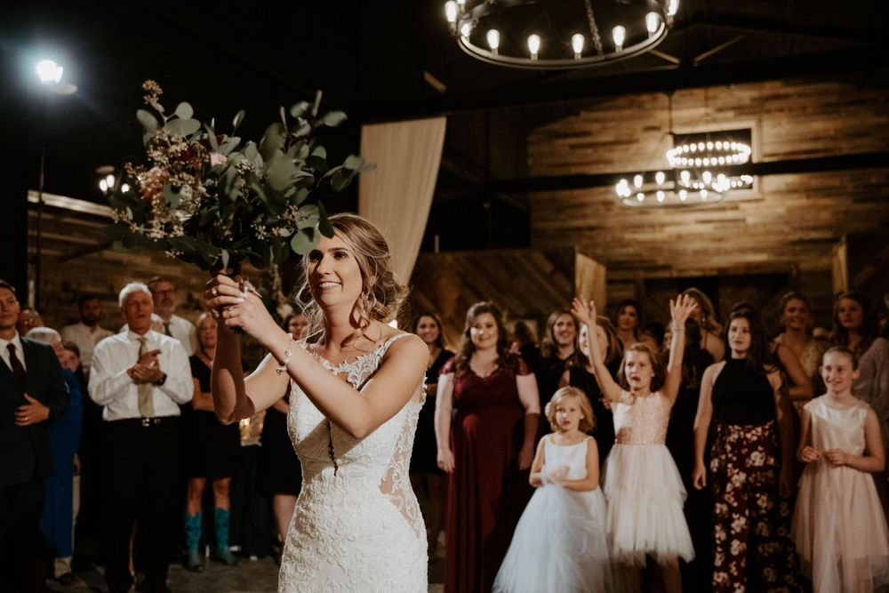 Bride tosses bouquet inside the wedding venue at The Reserve at Ranger Creek Ranch in Seymour, Texas