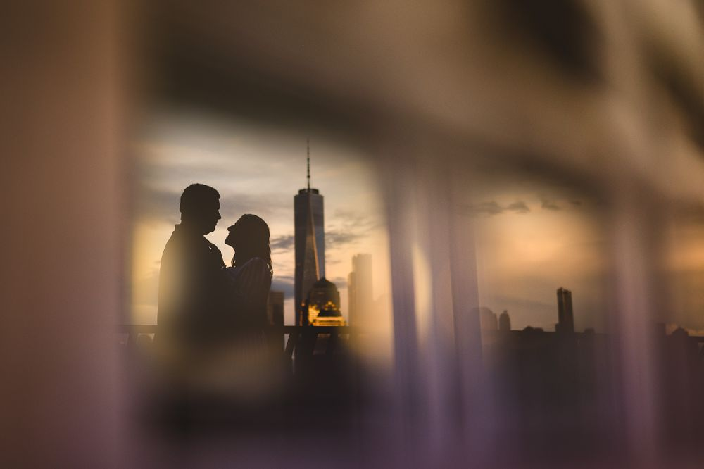 engaged couple reflection with New York skyline in background at jersey city waterfront
