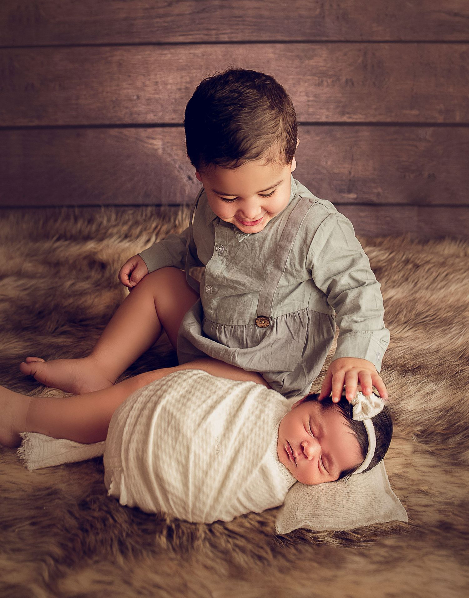 proud big brother and baby sister wrapped in white blanket