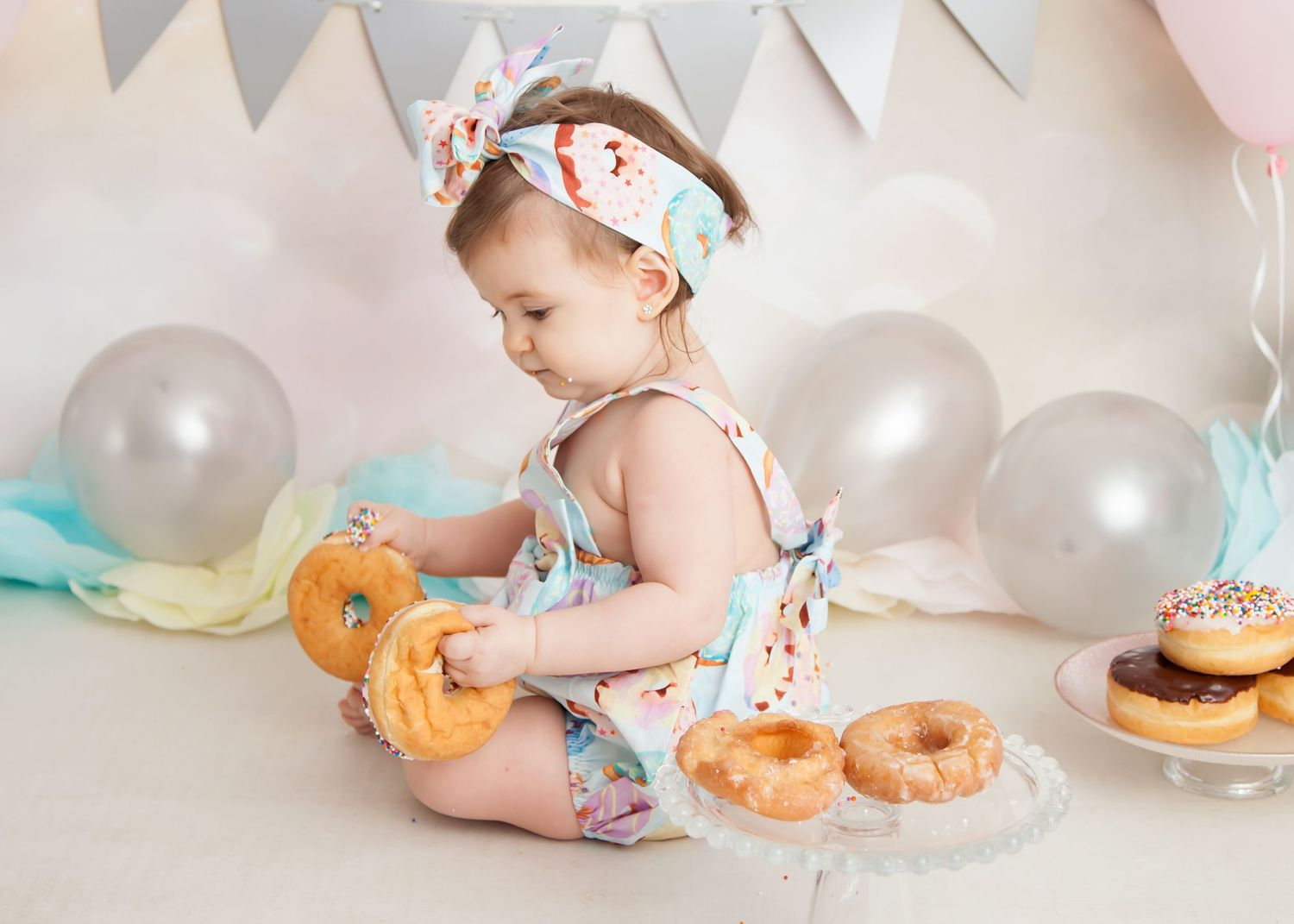 baby with donuts during cake smash photos
