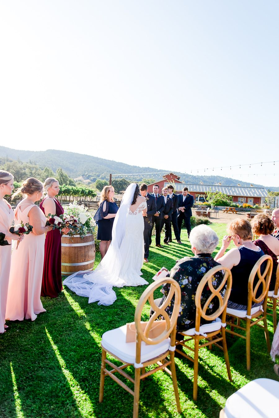bride and groom face each other in front of wedding guests at outdoor fall wedding on Pennyroyal Farm in North Cali