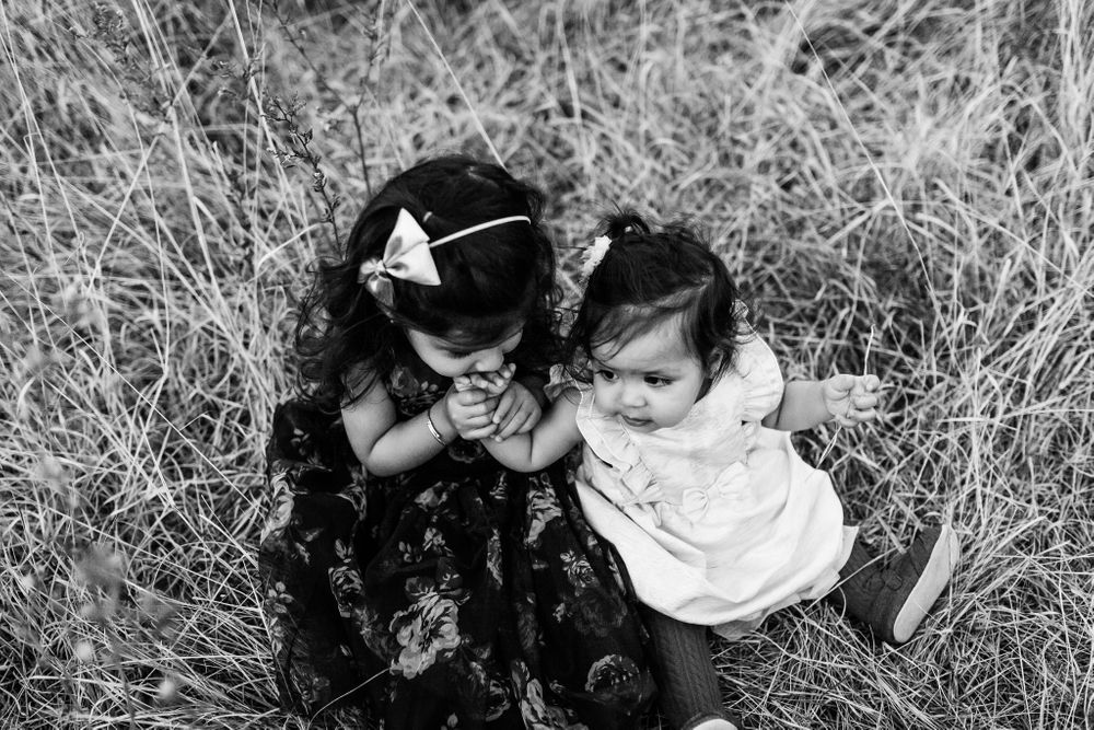 older sister kissing her little sister hands seating on the ground Chicago family lifestyle session