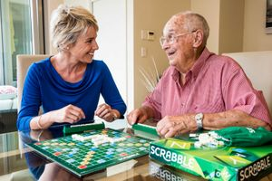a carer playing scrabble with her client'