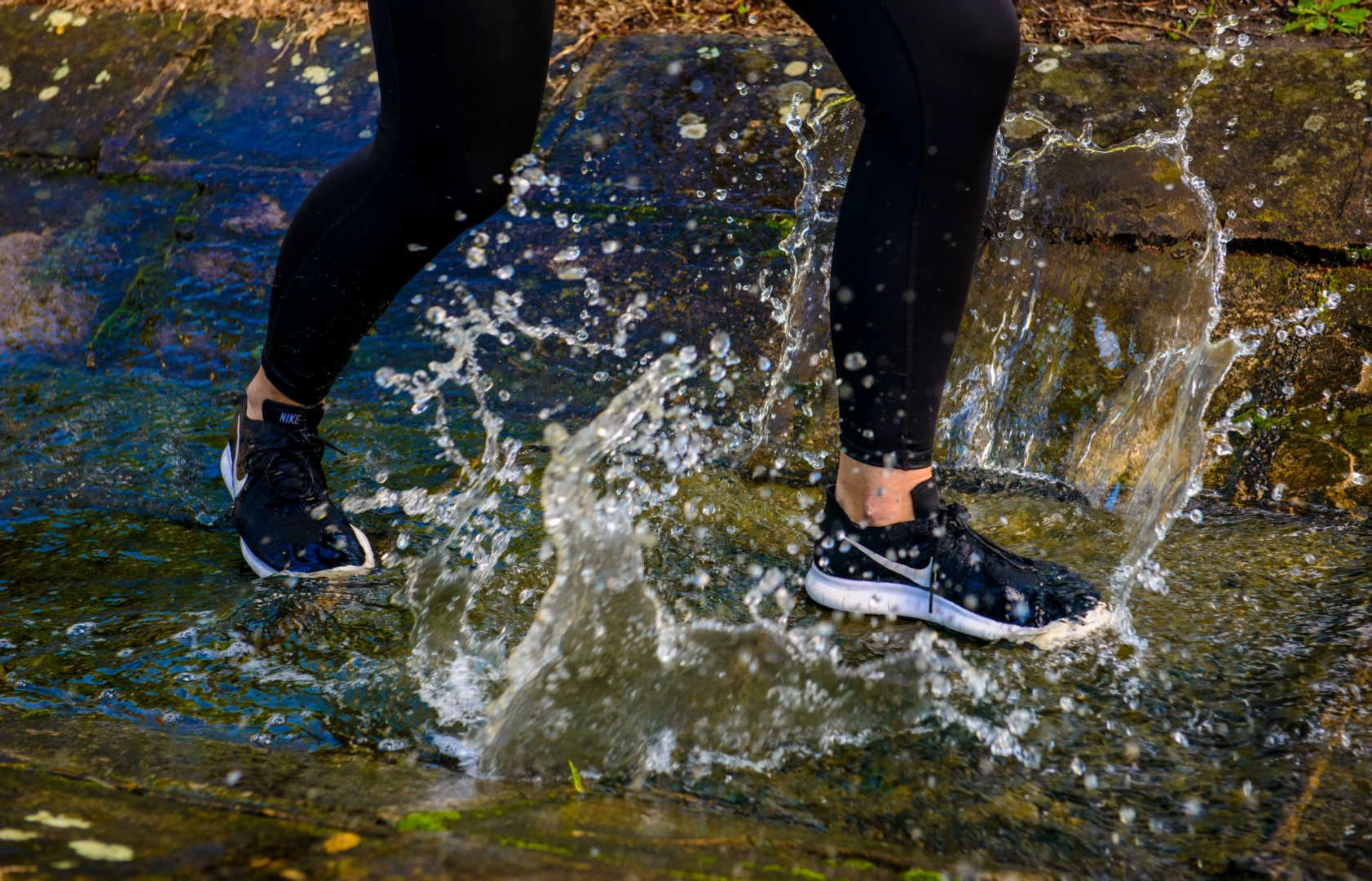 running shoes splashing through water
