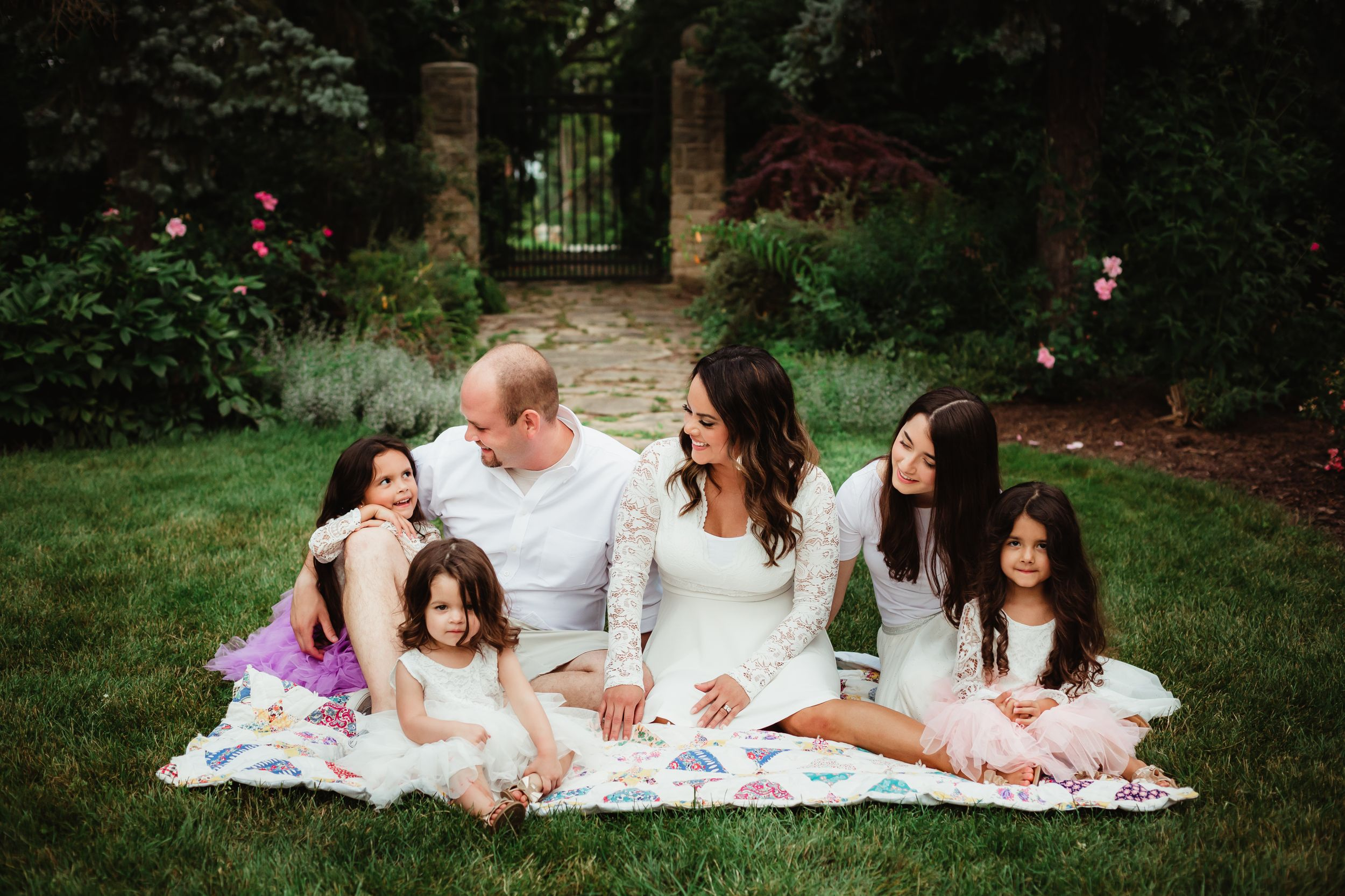 Family of six with all daughters sitting on a quilt and smiling at each other in Cooley Gardens.