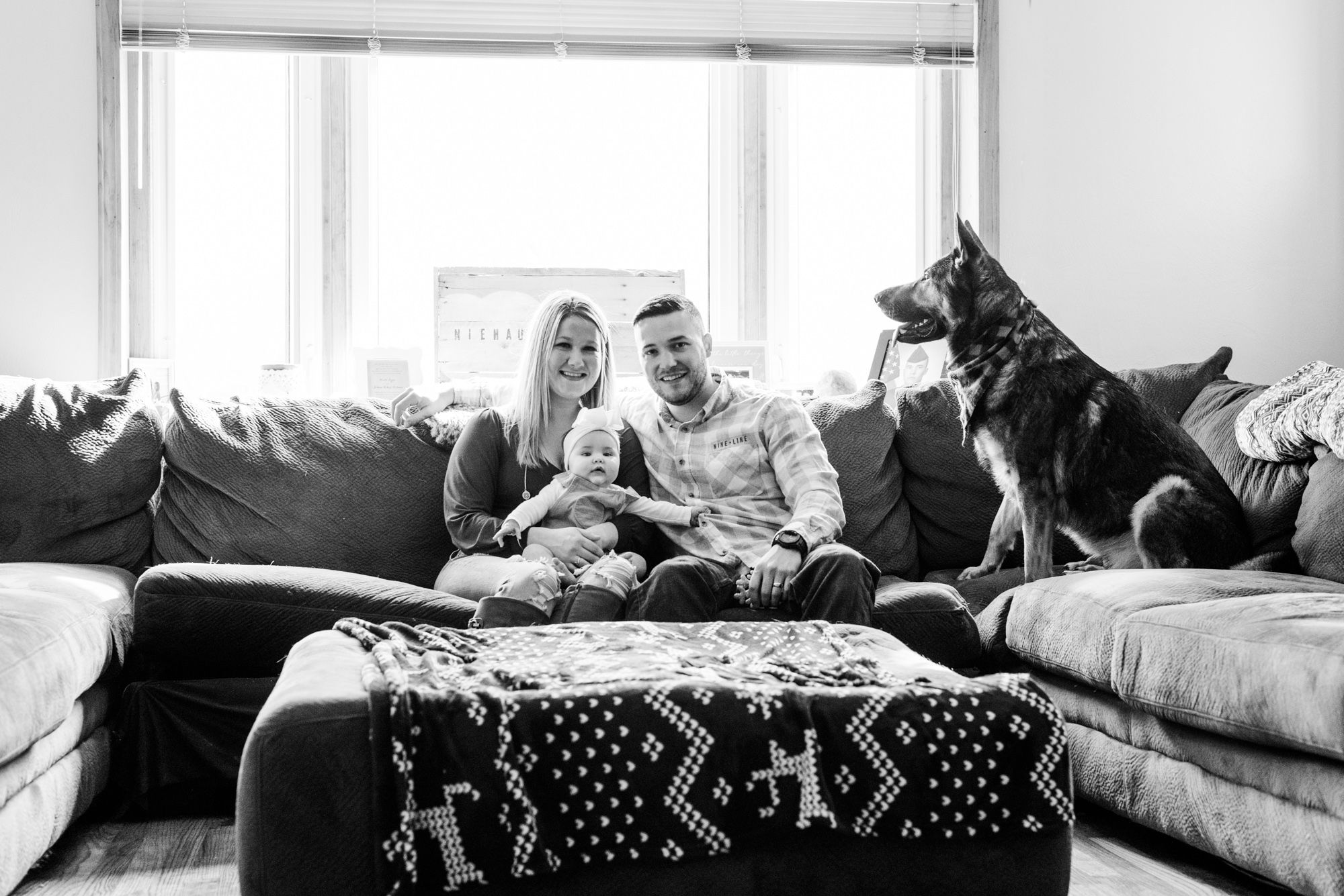 Lifestyle family photoshoot in the home with mom, dad, baby, and dog sitting on couch in Gibsonia, Pennsylvania