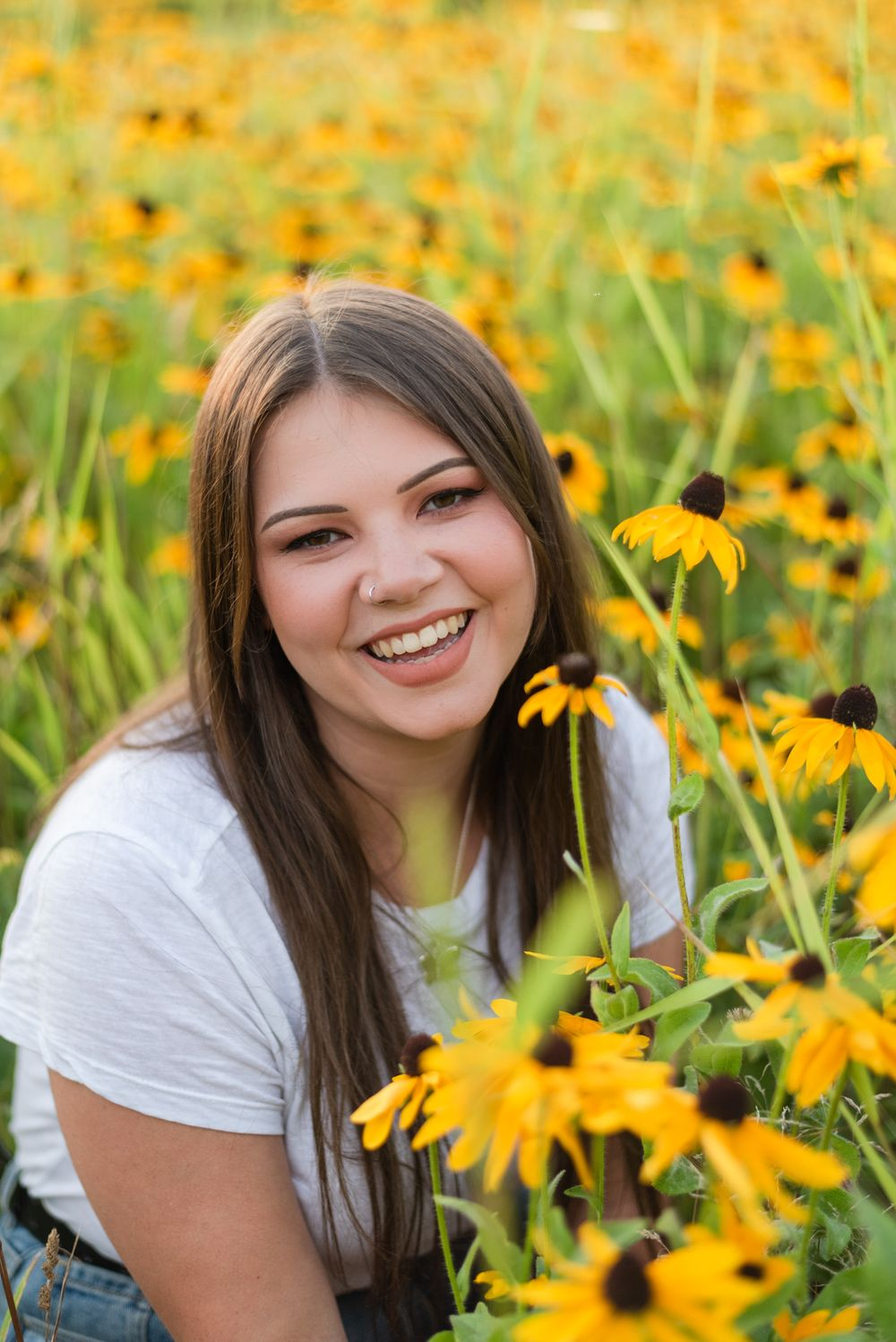 High school senior smiling in flower patch in golden sunlight at Hartwood Acres in Pittsburgh Pennsylvania