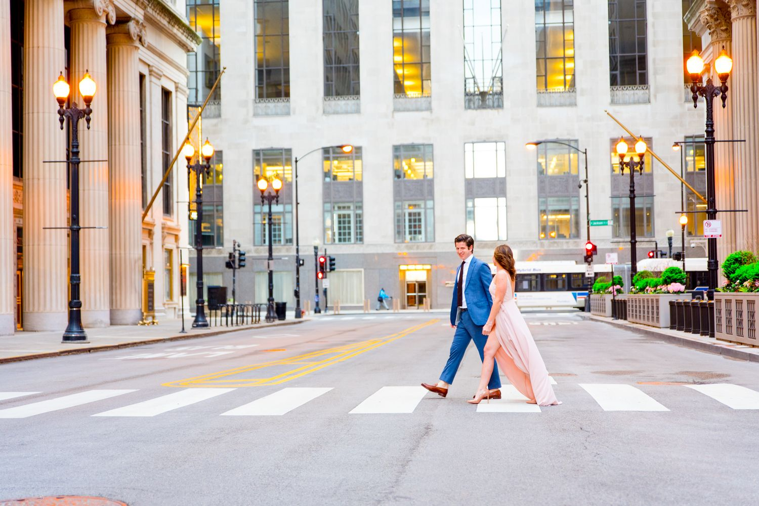 man in navy suit walking with woman in light pink dress in front of empty Chicago Board of Trade for engagement pictures