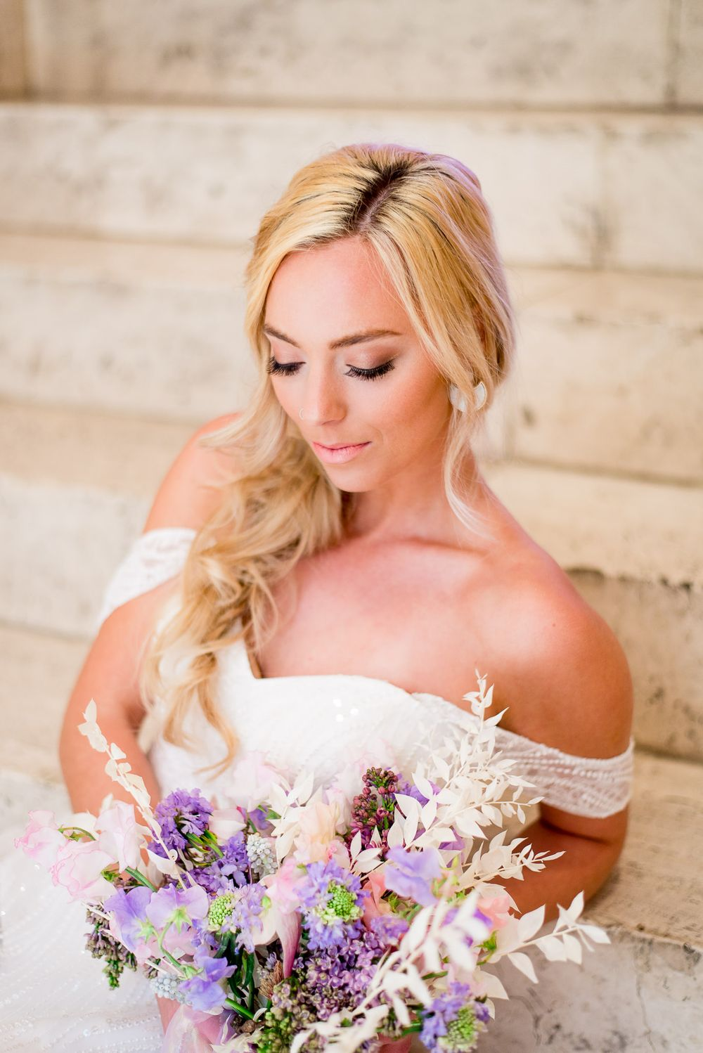 blonde bride with messy braid sitting on marble steps looking at pink purple white wedding bouquet