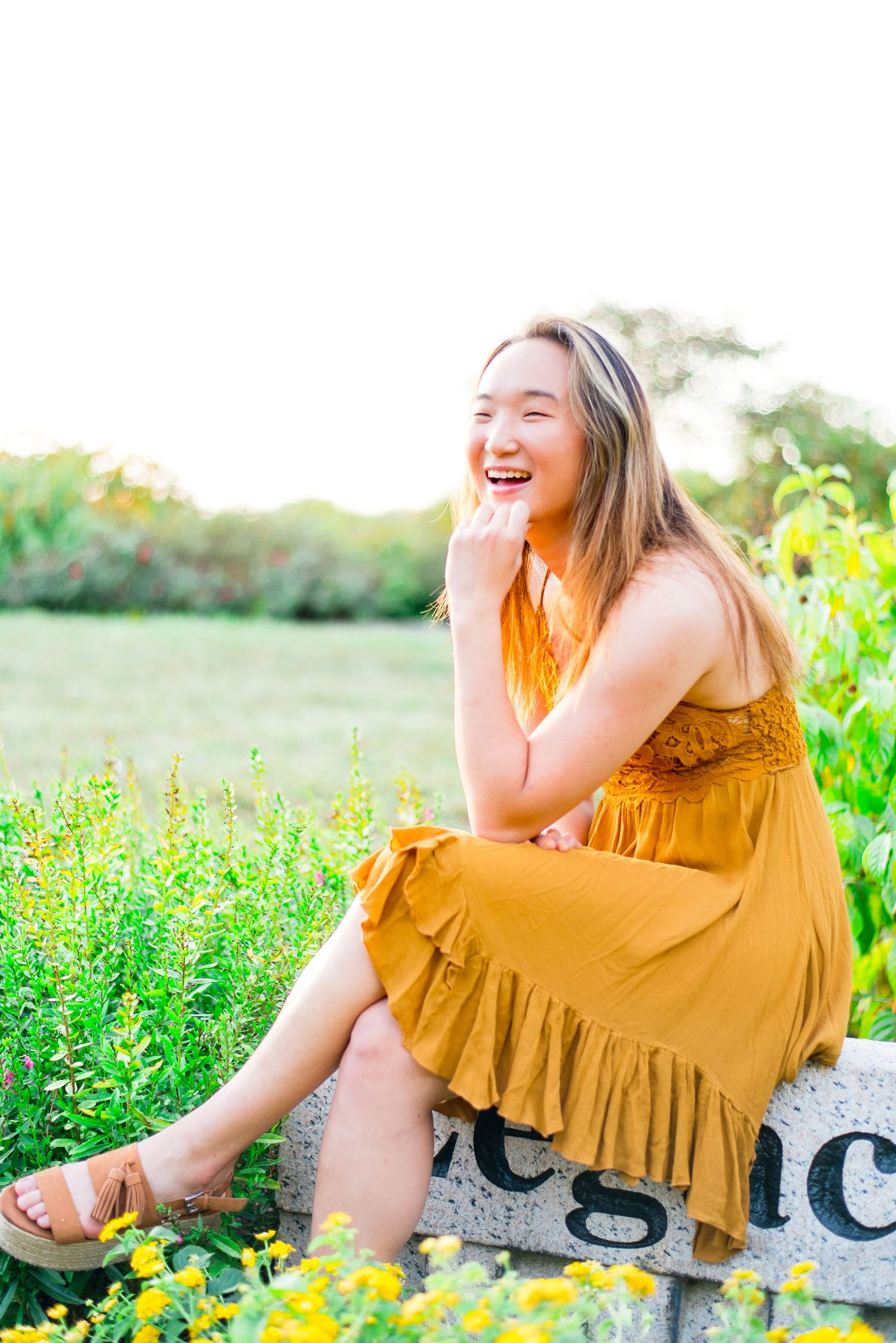 young woman in yellow dress sitting on a stone with knees crossed laughing