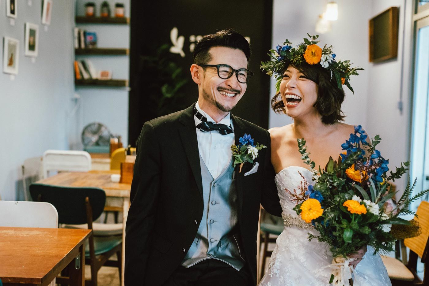 Elopement couple laughing together inside cafe