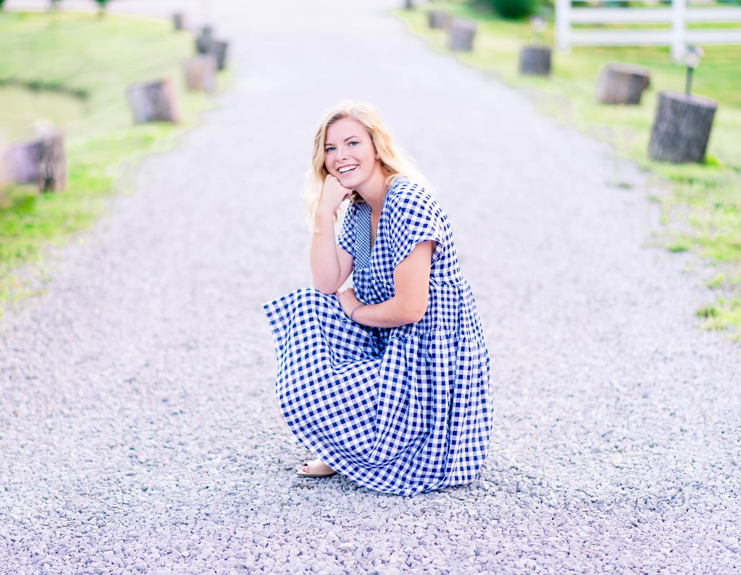 young woman in blue and white dress crouching on gravel path and smiling