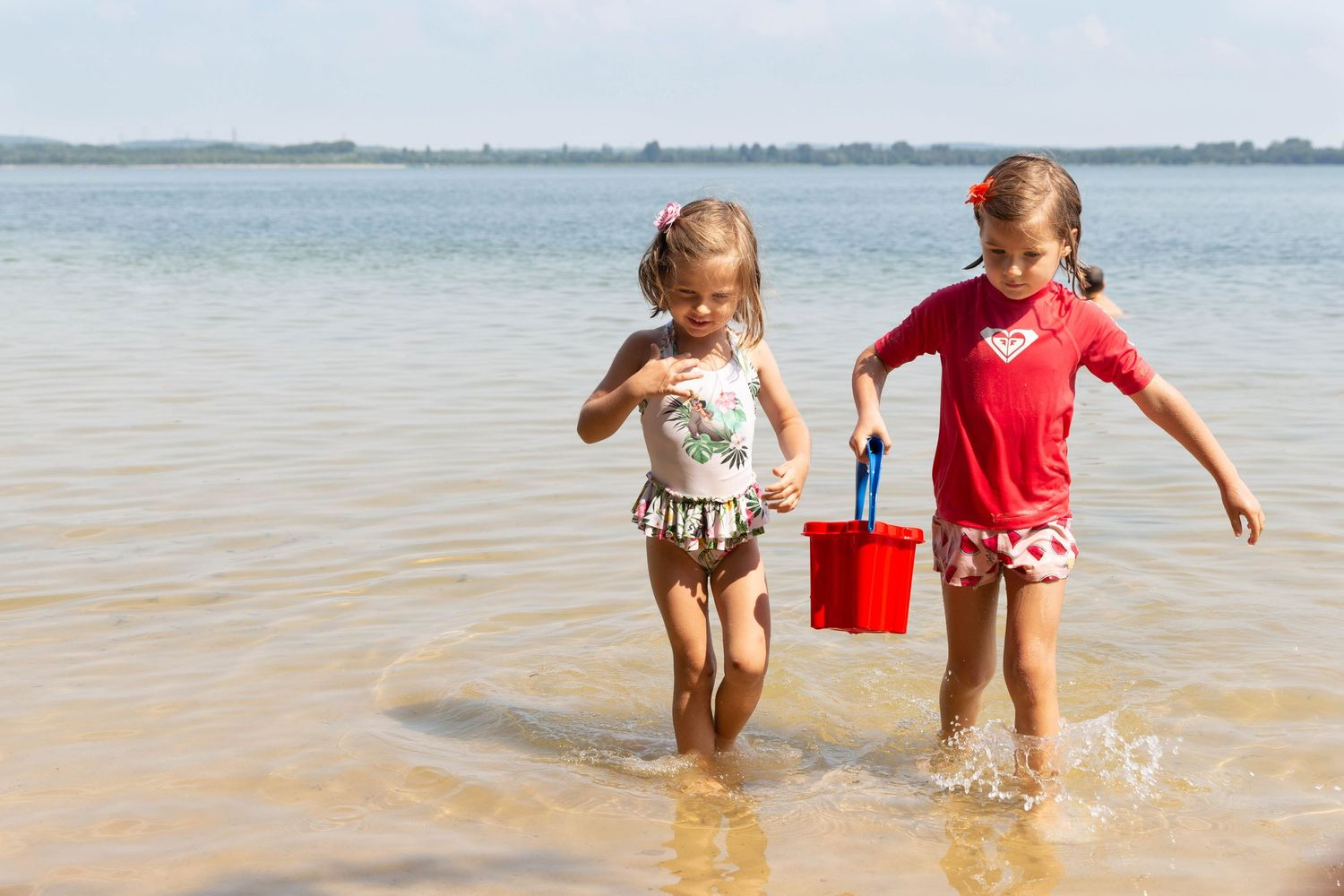 two girls coming out of sea with red bucket