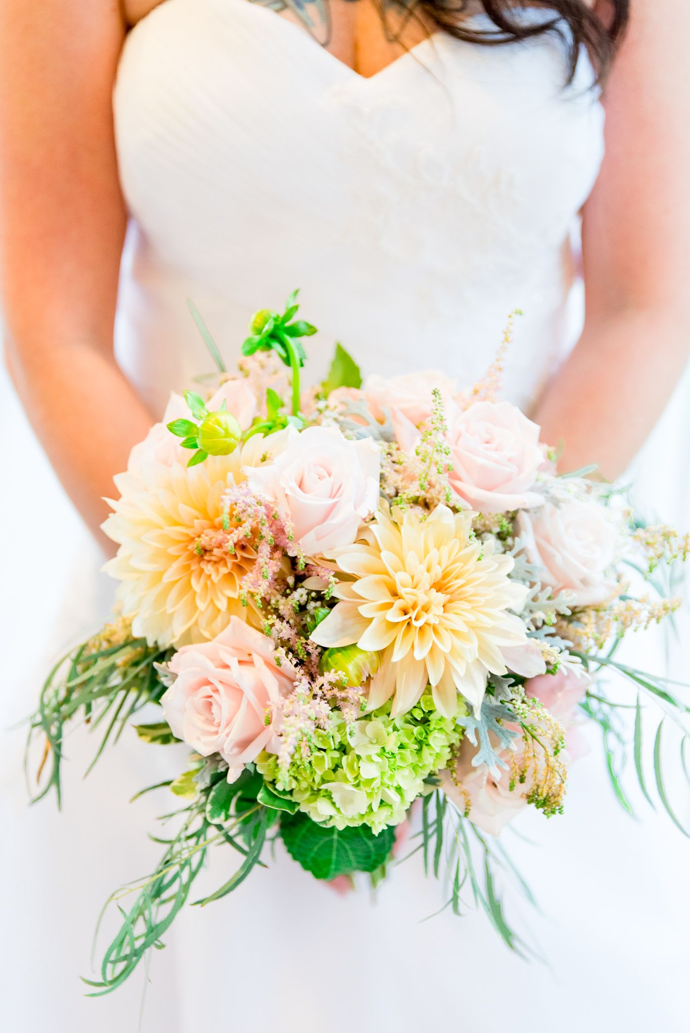 bride holding pastel yellow, pink, and neon green wedding bouquet for a fall or spring wedding