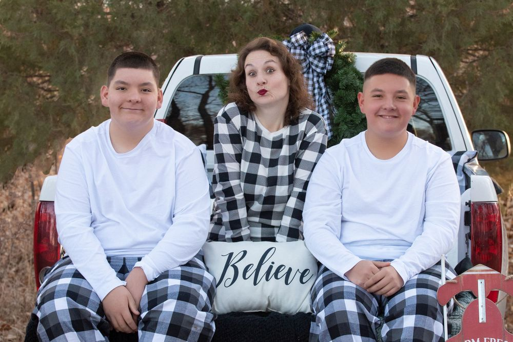 Mama and her 2 boys during their Christmas session in black and white buffalo plaid on a white truck