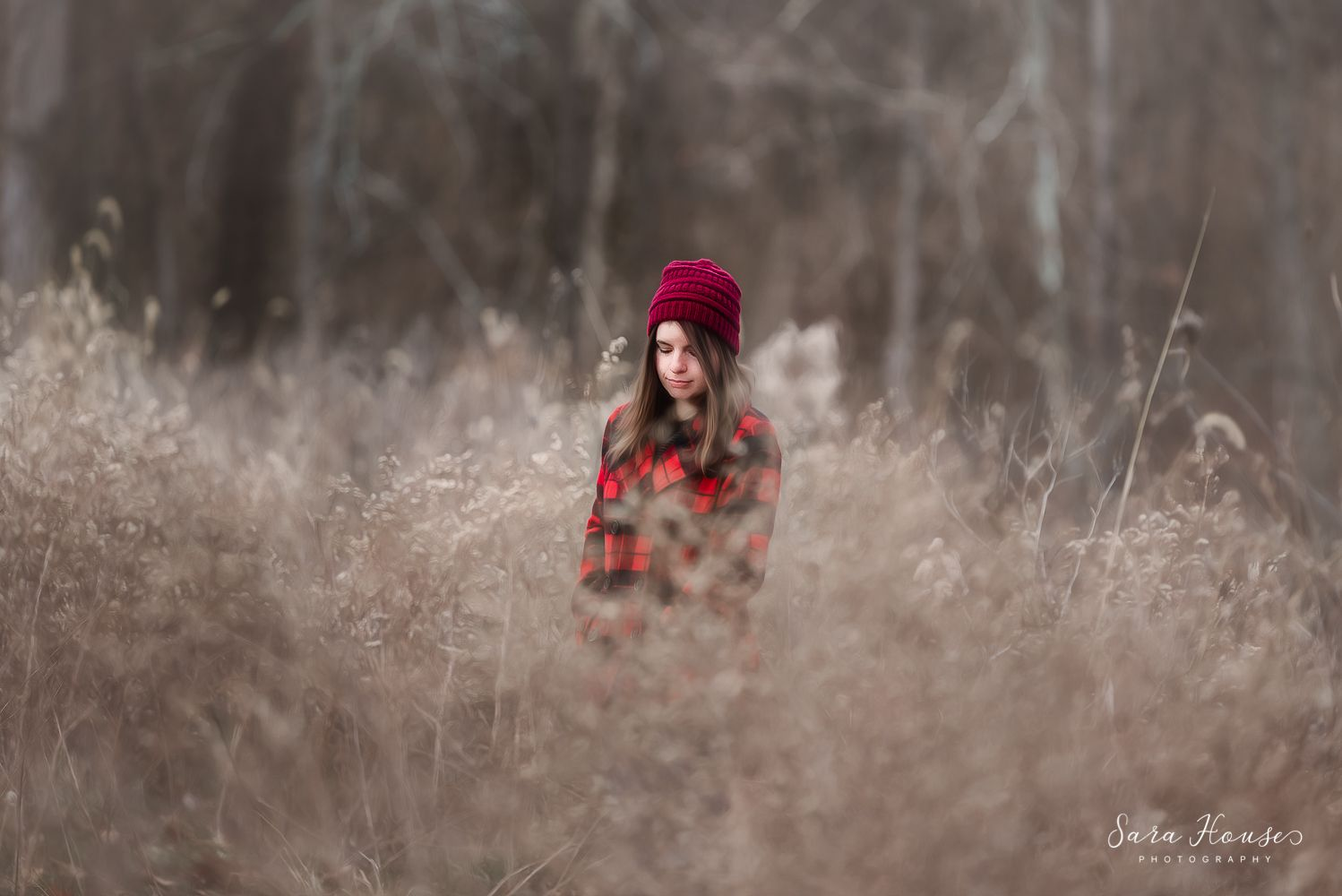 Girl in buffalo plaid coat and a maroon winter hat stands in a field of wildflowers in Plainfield Indiana