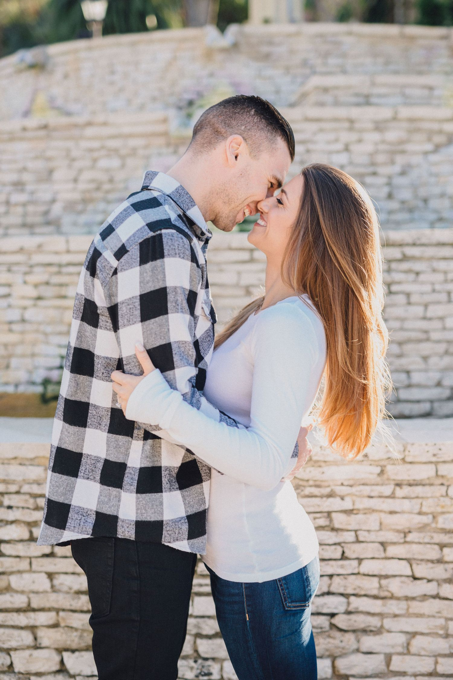 couple kiss in front of brick fountain