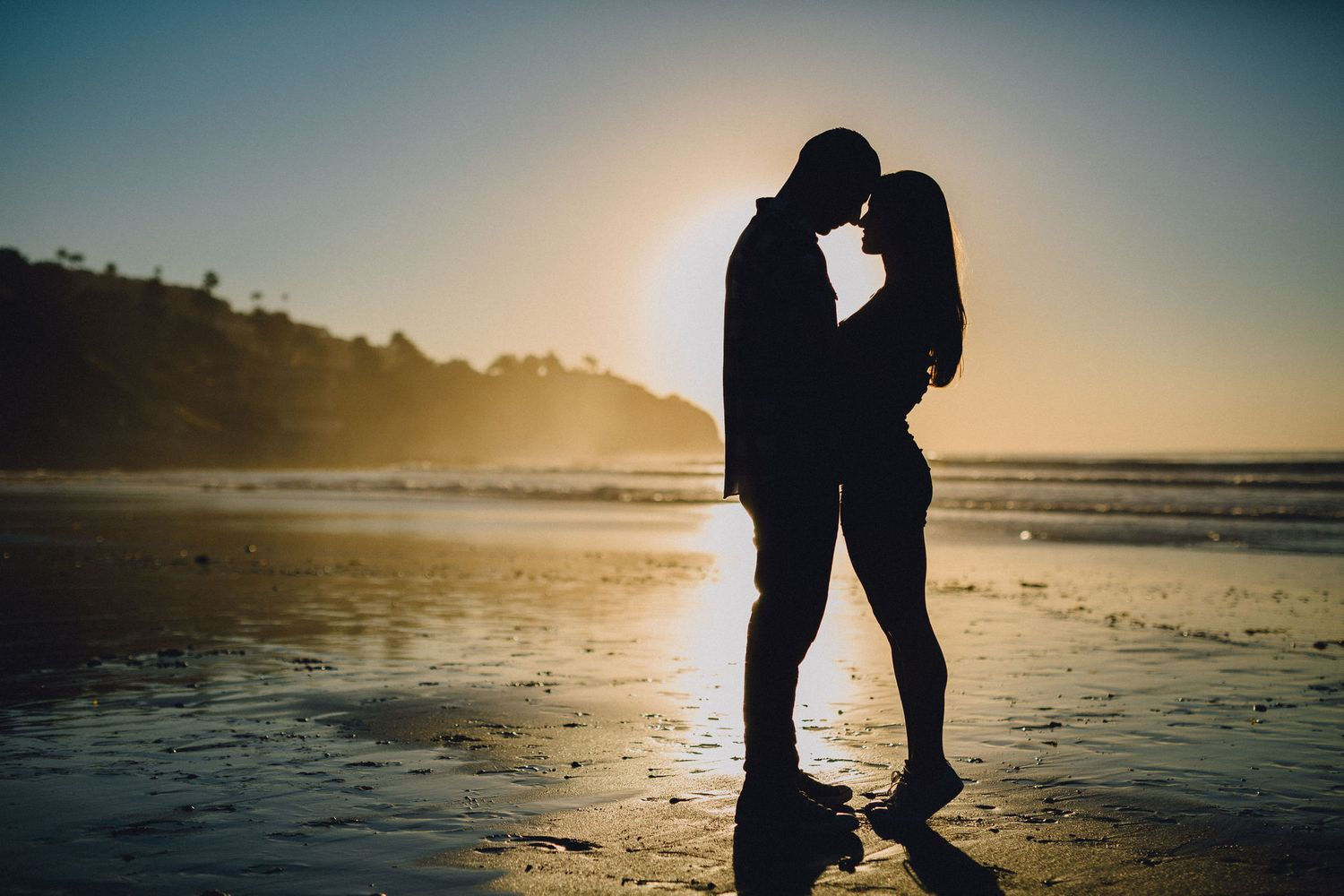 silhouette engagement photo at beach during sunset