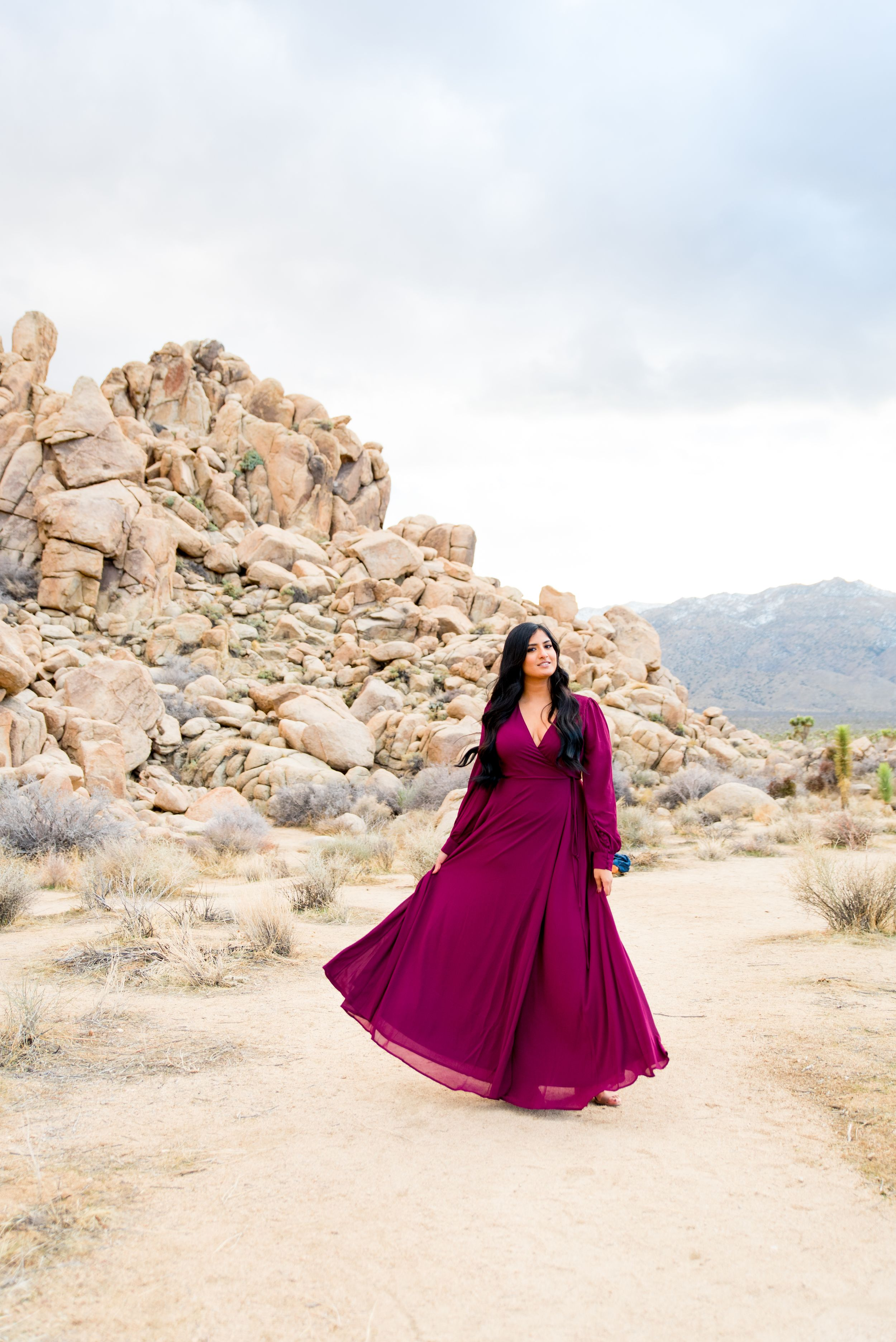 woman with long dark hair in red maxi dress looks to the side in front of boulders at Joshua Tree National Park